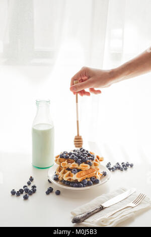 cropped shot of woman pouring honey from spoon on tasty waffles - Stock Photo
