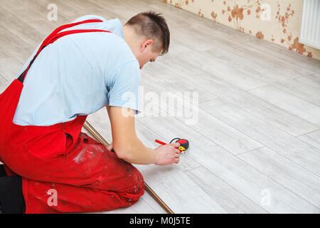 handyman laying down laminate flooring boards while renovating a house - Stock Photo
