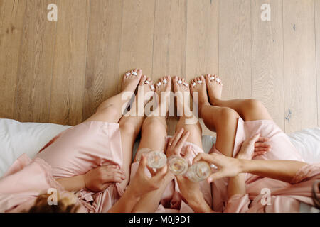 Top view of bridesmaids and bride sitting on bed and toasting champagne. Celebrating a bachelorette party at home. - Stock Photo