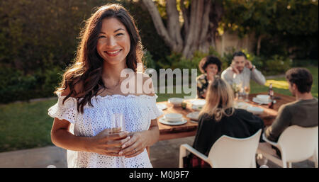 Beautiful asian woman standing outdoors with friends sitting in background having food. Woman with a drinks at outdoor - Stock Photo