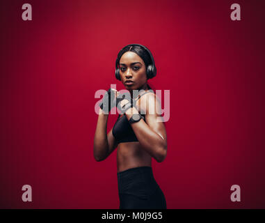 African young woman wearing boxing gloves posing in combat stance looking at camera. Fit young female boxer with - Stock Photo