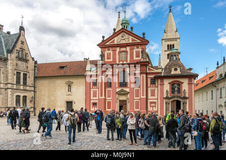 Crowds of visitors and tourists congregate outside St. George's Basilica, located within The Prague Castle complex - Stock Photo