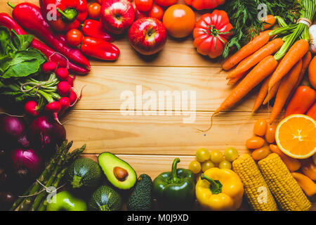 Frame full of fruits and vegetables on a wooden table seen from above with a negative space to place text or logo. - Stock Photo