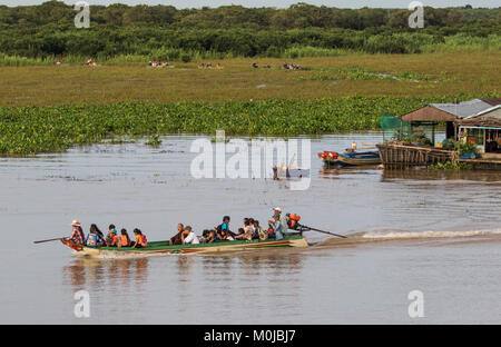 People in a public boat by a floating village in the Tonle Sap; Siem Reap, Cambodia - Stock Photo