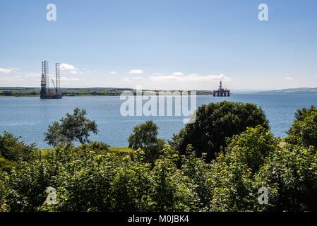 North Sea oil and gas rigs lined up in the sheltered waters of the Cromarty Firth for maintenance and refurbishment. - Stock Photo