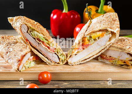Shawarma chicken roll in a pita with fresh vegetables and cream sauce on wooden background. Selective focus - Stock Photo