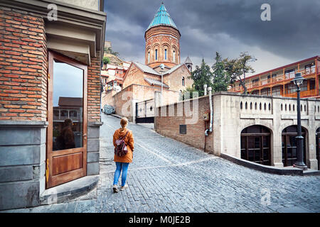 Tourist woman in brown jacket walking down the Old streets near church in central Tbilisi, Georgia - Stock Photo