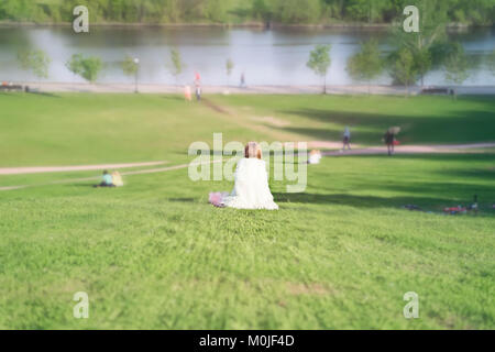 Girl,  in her clothes looking like   on a white angel, sits back - Stock Photo