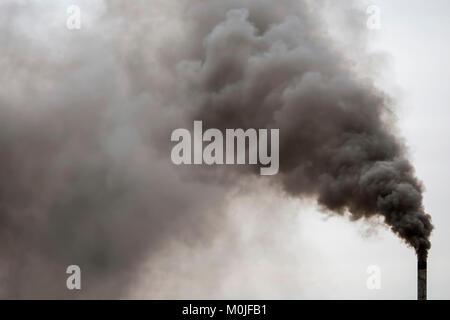 Factory chimney smoking, heavy black smoke on the sky. - Stock Photo