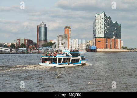 HANBURG, GERMANY- AUGUST 12, 2015: Boat with tourists goes on Elbe river towards Elbphilharmonie, a concert hall - Stock Photo