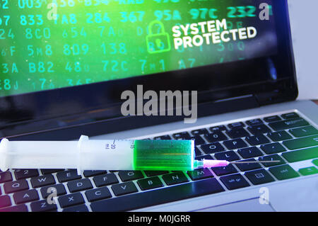 System protection concept and cybersecurity. Antivirus vaccination in the syringe applied to the computer. - Stock Photo