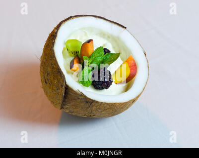 Half Coconut with Cream and Fresh Fruits Salad Still Life Composition - Stock Photo