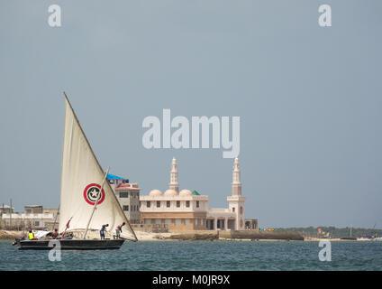 Dhow sailing in front of the new Lamu mosque, Lamu, Lamu Archipelago, Kenya - Stock Photo