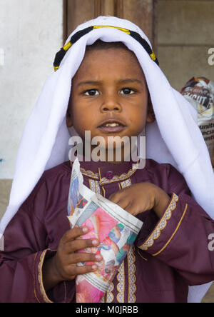 Young boy in traditional suit dressed for the Mawlid festival, eating popcorn, Lamu Island, Kenya - Stock Photo