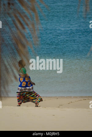 Woman with colorful kaftan crossing Kizingoni beach, Lamu, Kenya - Stock Photo