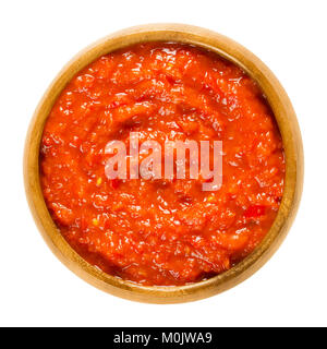 Ajvar in wooden bowl. Condiment made of bell peppers, used in Balkan cuisine. Bread spread or side dish. Also called - Stock Photo