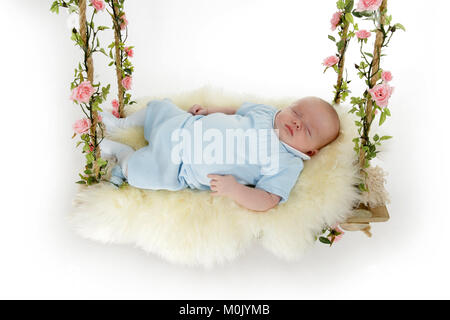 2 month old baby boy sleeping on rustic swing - Stock Photo