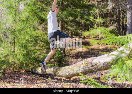 Young happy man running jogging jumping over fallen tree branch in autumn, fall, summer pine forest in mid-air - Stock Photo