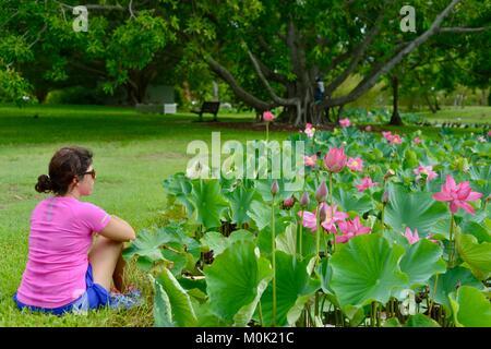 Women with pink sports top enjoying Anderson Park Botanic Gardens, Townsville, Queensland, Australia - Stock Photo