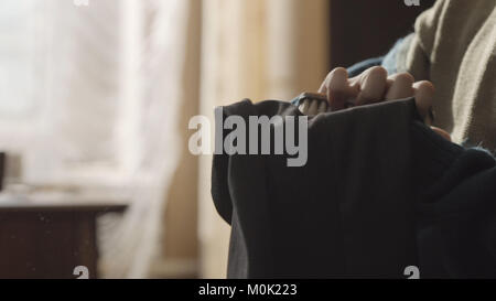 Woman using a lint brush to remove debris from her dress. Woman brushing her pants using a brush close up. Woman's - Stock Photo