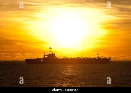The U.S. Navy Nimitz-class aircraft carrier USS George Washington steams underway at sunset July 8, 2012 in the - Stock Photo