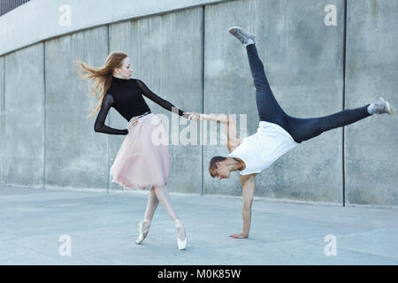 A young couple in love passionately dances on a city street. Dancer and sportsman Parkour. Balance and stunts in - Stock Photo