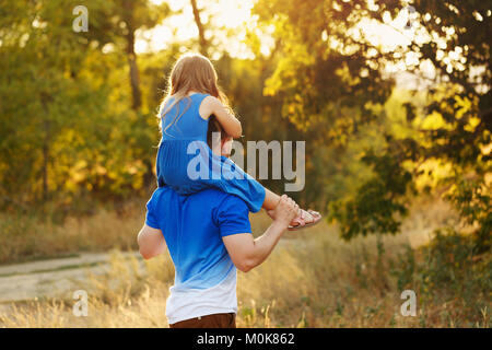 Father carrying daughter piggyback. Family holiday. A walk in the city park at sunset - Stock Photo