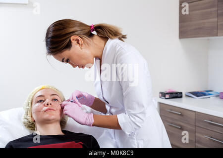 Close-up of a woman azian beautician in a medical dressing gown and sterile gloves makes a woman injecting Botox - Stock Photo