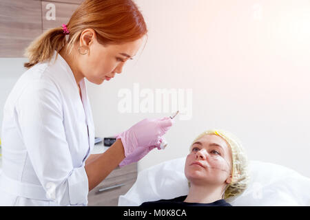 Young woman doctor cosmetician in white lab coat and sterile gloves makes injection of hyaric acid using a syringe - Stock Photo