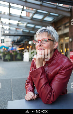 Portrait of a mature woman in a red leather jacket sitting at a table outside a shop with her chin resting in her - Stock Photo