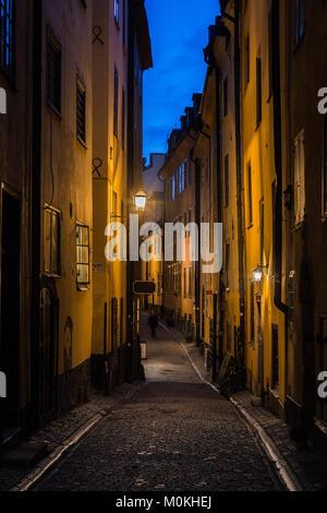 Charming street scene in Stockholm's historic city center Gamla Stan (Old Town) illuminated in beautiful twilight - Stock Photo