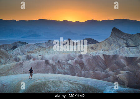 Hiker standing at famous Zabriskie Point viewpoint in beautiful golden evening light at sunset in summer, Death - Stock Photo