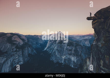 A fearless hiker is standing on an overhanging rock looking towards famous Half Dome in Yosemite National Park in - Stock Photo