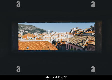 Looking out of a window at red colored terra-cotta rooftops in the historic town of Dubrovnik in beautiful evening - Stock Photo