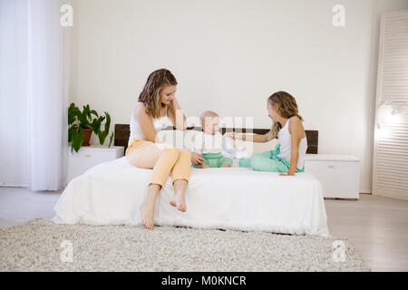 three girls play sisters in the morning on the bed in the bedroom - Stock Photo