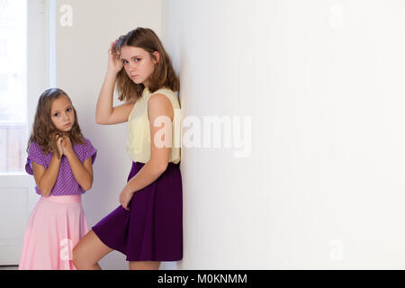 two girls sisters in colored dresses posing - Stock Photo