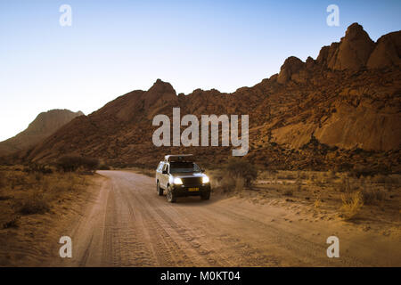 A 4x4 vehicle with headlights illuminating drives on a desert road framed by mountains and fading sunset light. - Stock Photo