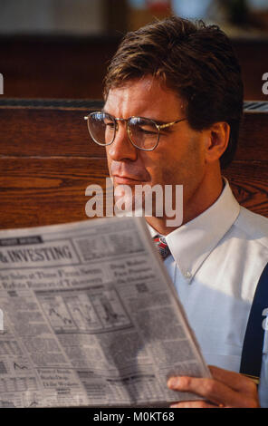 A commuter reads a financial newspaper in a train station as waits. - Stock Photo