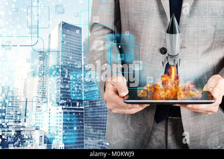 Businessman launches rocket from a tablet. concept of company startup - Stock Photo