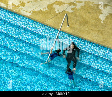 Muslim mother wearing a religious swimming costume with her children, Sandakan, Sabah, Borneo, Malaysia - Stock Photo