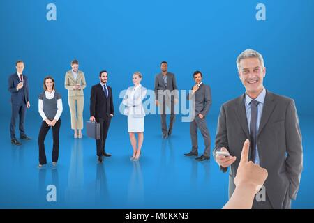 Hand choosing a business man on blue background with business people - Stock Photo