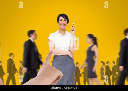 Hand choosing a business woman on yellow background with business people walking - Stock Photo