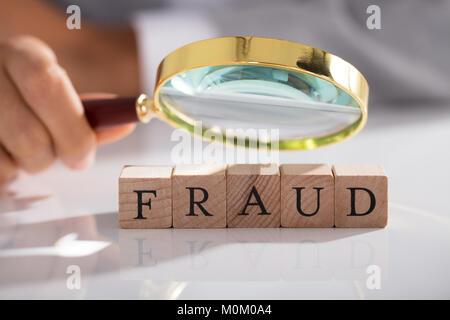 Person Examining Fraud Blocks Through Magnifying Glass On White Desk - Stock Photo