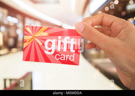 Cropped Image Of Person's Hand Holding Gift Card - Stock Photo