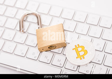 Digital currency, silver bitcoin with open padlock on keyboard - Stock Photo