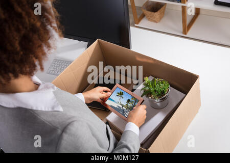 Close Up Of A Businesswoman Packing Picture Frame In Cardboard Box
