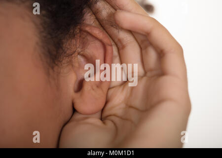 Close-up Of Person Trying To Hear With Hand Over Ear - Stock Photo