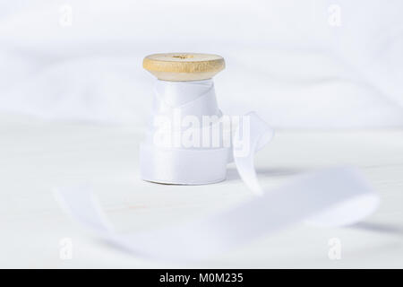 Single Wooden Spool Roll with Silk Ribbon on White Cotton Linen Fabric Background. Sewing Crafts Hobby Concept. - Stock Photo