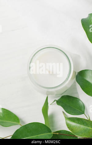 White Candle in Glass Jar Ficus Tree Branch with Young Fresh Green Leaves on White Wood Background. Styled Stock - Stock Photo