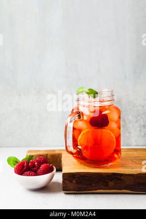 summer refreshing drink with ice and fresh ripe berries. raspberries and blackberries with citrus on a stone background - Stock Photo